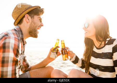 Jeune couple à la plage s'amuser, rire et boire de la bière Banque D'Images