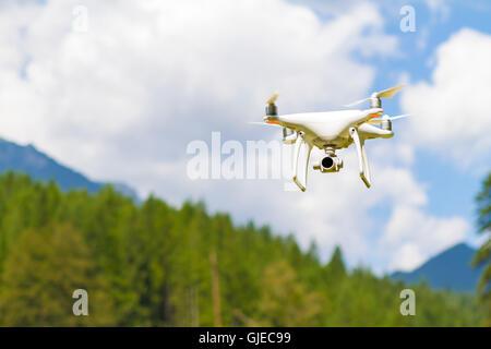 Bourdon blanc quad copter avec appareil photo numérique haute résolution volant dans le ciel bleu sur la montagne Banque D'Images