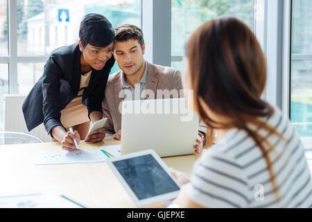 Groupe de travail d'affaires avec ordinateur portable, tablette et téléphone cellulaire sur réunion d'affaires Banque D'Images