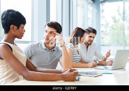 Groupe de jeunes gens d'affaires assis et talking in office Banque D'Images