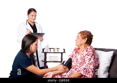La mesure de la pression artérielle sur l'infirmière Senior woman alors que médecin, prend des notes. Banque D'Images