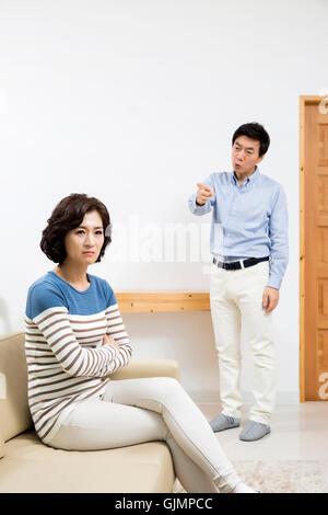 Asiatique d'âge moyen Couple having an Argument in Livingroom Banque D'Images