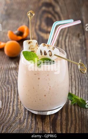 Fruits d'été frais fait maison avec de la guimauve grillée et milkshake abricots mûrs sur fond de bois rustique Banque D'Images