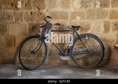 Un vieux vélo pédale s'appuie contre un mur de pierre. Un sac est suspendu au guidon Banque D'Images