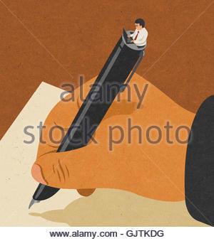 L'homme écrit avec stylo plume en contraste avec l'aide d'un ordinateur portable Banque D'Images