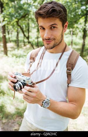 Beau jeune homme avec sac à dos en prenant des photos avec l'appareil photo photo ancienne en forêt Banque D'Images