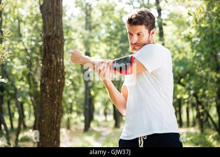 Athletic young sportsman avec téléphone mobile en handband debout et faisant des exercices en forêt Banque D'Images
