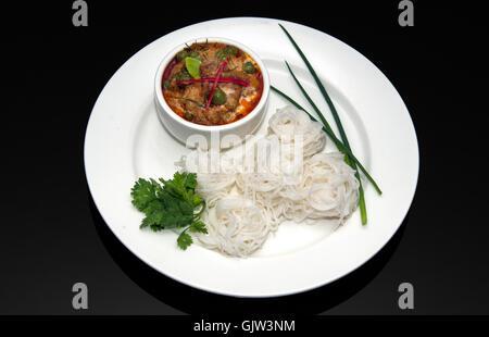 Thai Red curry de boeuf, nouilles de riz blanc sur fond noir Banque D'Images