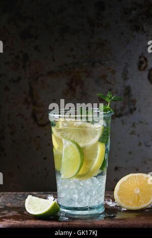 Limonade citron et lime fait maison, servi en verre avec de la glace et de menthe fraîche, oveer fond rusty dark Banque D'Images