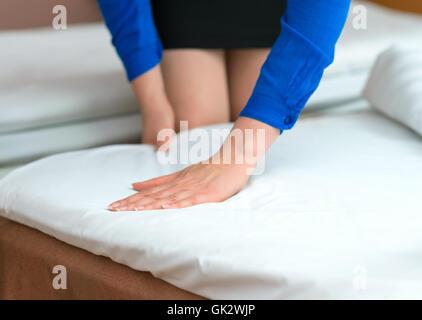 Un service de chambre. Femme faisant lit dans chambre d'hôtel. Banque D'Images