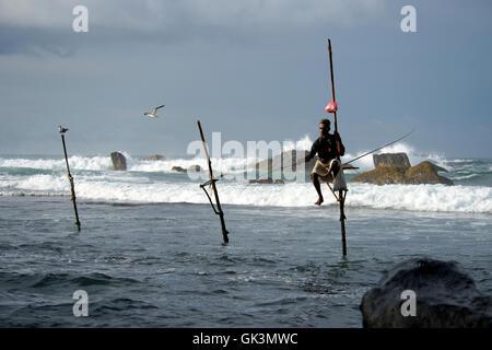 Sri Lanka --- Stilt fisherman la capture de poissons apportés par de grosses vagues, Weligama, au Sri Lanka --- Banque D'Images