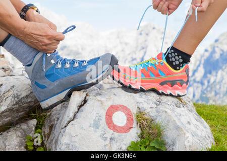 Deux randonneurs attachant lacets, haut dans les montagnes
