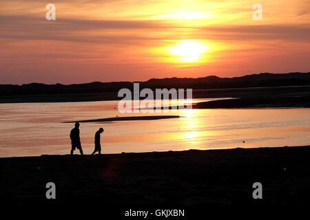 Deux personnes sur la plage au coucher du soleil en silhouette Banque D'Images