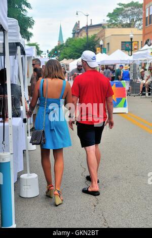 Un jeune couple parcourir les stands dans les rues qui ont été fermées pour accueillir une foire d'art de rue. Elgin, Banque D'Images