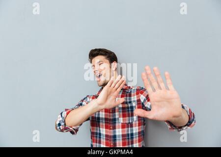 Bel homme montrant le geste d'arrêt avec des paumes isolé sur fond gris Banque D'Images