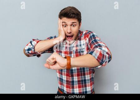 48ab560ea83ba L'étonnement jeune homme en chemise à carreaux à la montre-bracelet sur  fond gris à Banque D'Images, Photo Stock: 115439601 - Alamy