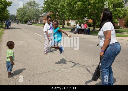 Detroit, Michigan - Un garçon saute à une corde summer street juste tenue par un groupe local. Banque D'Images