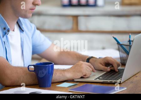 Man working on laptop in home office dans l'intérieur de l'espace loft. Beau mec sérieux en bois à assise avec un ordinateur portable