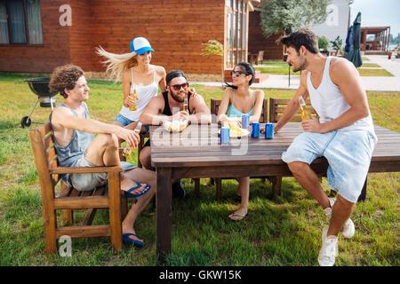 Groupe de professionnels jeunes assis à la table et boire de la bière en plein air Banque D'Images