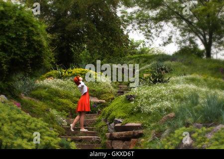 Portrait d'une belle jeune fille en robe orange dans une forêt féerique Banque D'Images