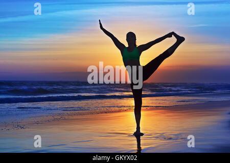 Silhouette de femme noire qui s'étend à yoga retreat sur le coucher du soleil, plage de sable, ciel coloré fond Banque D'Images