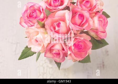 Roses roses dans un vase blanc Banque D'Images