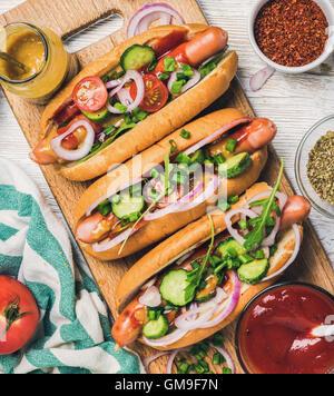 Des hot-dogs avec des légumes, du ketchup, de la moutarde et d'épices