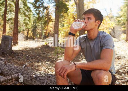 Coureur de sexe masculin dans une forêt prend une pause pour s'asseoir et boire de l'eau Banque D'Images