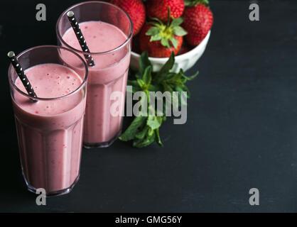 Smoothie aux fraises et à la menthe dans des grands verres, criailler de baies fraîches sur fond de bois rustique Banque D'Images