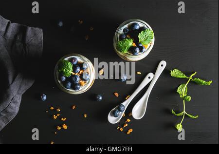 Petit-déjeuner sain. Yaourts aux myrtilles granola avoine et de feuilles de menthe dans des bocaux en verre sur Banque D'Images