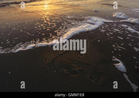 Figure cœur percé par une flèche tracée sur la plage de sable fin baignée par les vagues. Banque D'Images