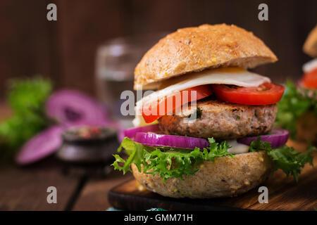 Hamburger (Sandwich) avec burger de poulet, salade, tomate, œuf frit et sauce tartare Banque D'Images