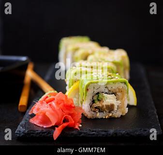 La cuisine japonaise traditionnelle - rouleaux de sushi, et la sauce sur un fond noir. Banque D'Images