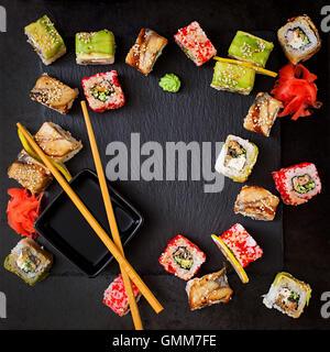 La cuisine japonaise traditionnelle - rouleaux de sushi, et la sauce sur un fond noir. Vue d'en haut Banque D'Images