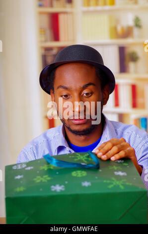 Charmant homme portant chemise bleue et hat sitting by table d'anniversaire de l'ouverture, à la célébration, excité Banque D'Images