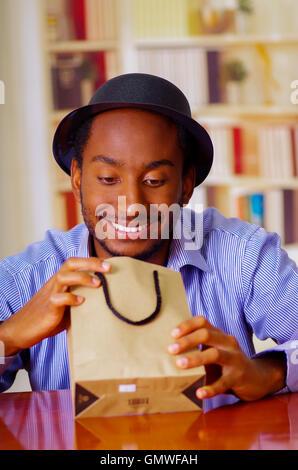 Charmant homme portant chemise bleue et hat sitting by table d'anniversaire de l'ouverture, à la hâte, célébrant Banque D'Images
