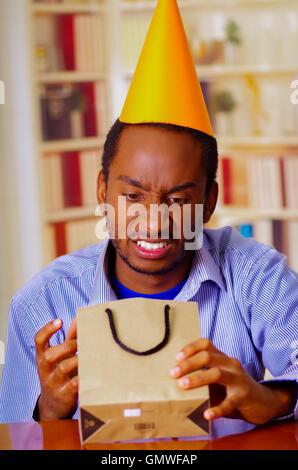 Charmant homme portant chemise bleue et hat sitting by table d'anniversaire de l'ouverture, à la colère, célébrer Banque D'Images