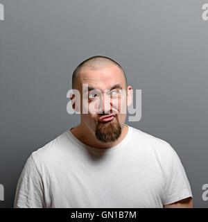 Portrait d'un homme faire drôle de visage contre l'arrière-plan gris Banque D'Images