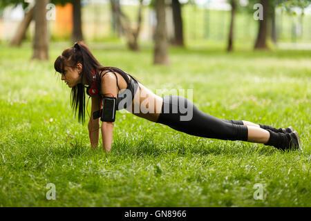 Mettre en place en faisant des écouteurs brunette plank core l'exercice sur l'herbe Banque D'Images