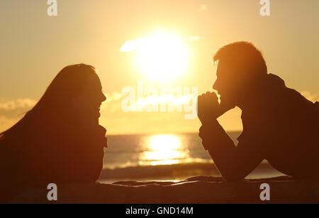 Profil d'un couple d'ossature à l'autre au coucher du soleil sur la plage avec le soleil au milieu et une lumière Banque D'Images