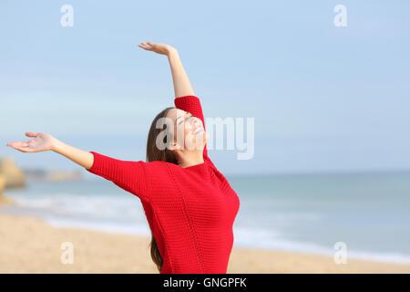 Portrait d'une femme joyeuse heureux excité et raising arms portant un chandail rouge à la plage dans un matin ensoleillé
