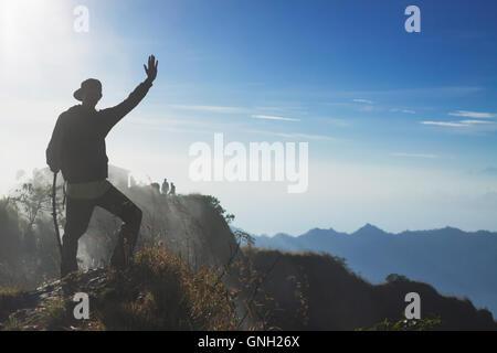 Silhouette d'un homme debout sur une montagne en agitant, Mont Batur, Bali, Indonésie Banque D'Images