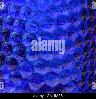 En verre bleu foncé en pointillés pour les fonds. Verre bleu pétillant comme liquide. Banque D'Images