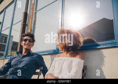 Coup de jeune homme et femme assise à l'extérieur et de parler. Jeune couple de passer du temps ensemble. Banque D'Images