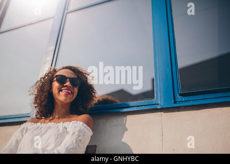 Coup de jeune femme africaine assis à l'extérieur à l'écart et souriant. Femme portant des lunettes de soleil assis dehors à la h Banque D'Images