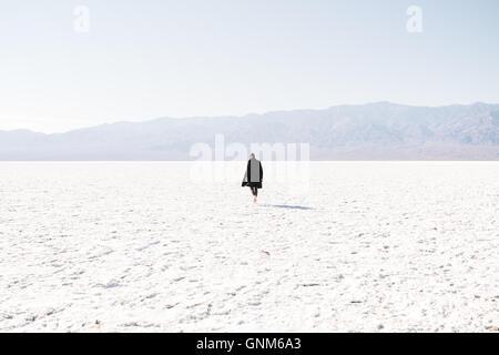Un homme marche à travers les plaines salines dans Death Valley National Park Banque D'Images