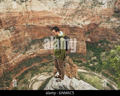 Un randonneur se trouve au sommet d'un pic dans l'Utah Zion National Park Banque D'Images