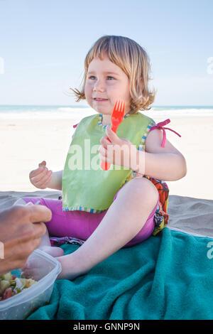 Deux ans avec enfant bib vert assis sur la serviette de plage parasol parasol à manger la salade de thon avec fourchette Banque D'Images