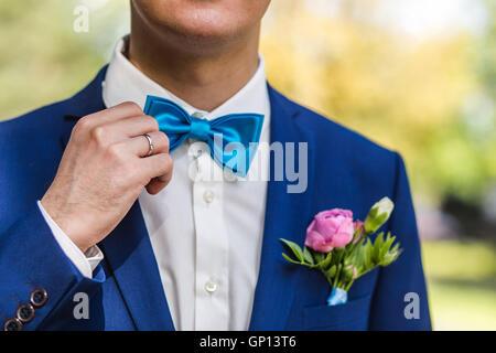 Le marié se redresse une cravate. Gros plan de l'dans le parc le jour de leur mariage. Banque D'Images