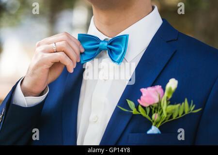 Le marié élégant se redresse une cravate . Gros plan de l'habillé en veste bleue et chemise blanche au parc le jour Banque D'Images